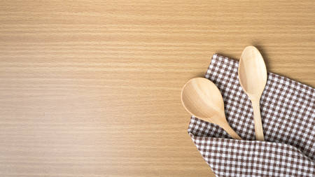 wood spoon and kitchen towel on table