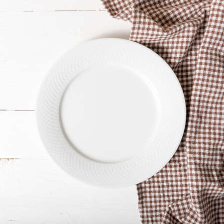 dishtowel: empty dish with kitchen towel over white table background