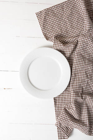 dishcloth: empty dish with kitchen towel over white table background