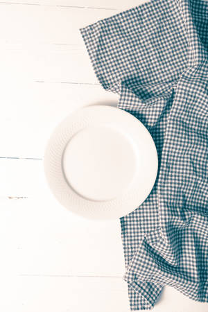 dishtowel: empty dish with kitchen towel over table background vintage style