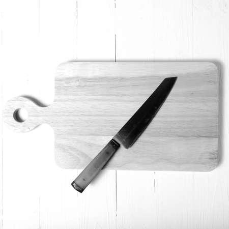 cuchillo de cocina: kitchen knife on cutting board over table background black and white tone color style Foto de archivo