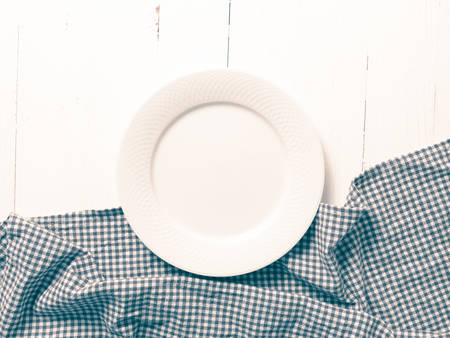 dishcloth: empty dish with kitchen towel over table background vintage style