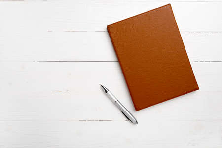 spiral notebook: brown notebook and pen on white table view from above