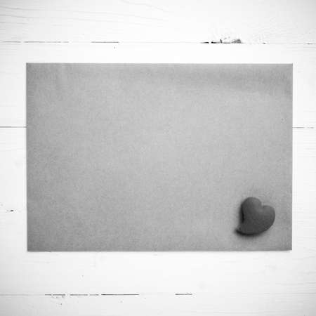 card design: heart on brown paper over white table black and white tone color style