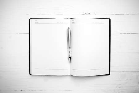 notebook paper: open notebook with pen on white table black and white style