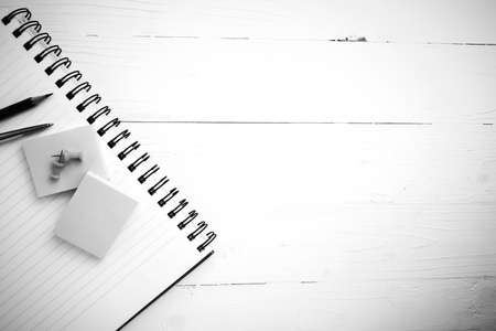 notepad with office supplies on white table view from above black and white style
