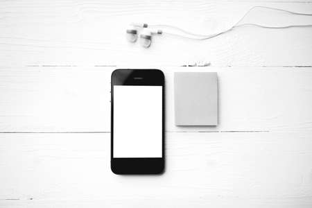cellphone and sticky note over white table black and white color style