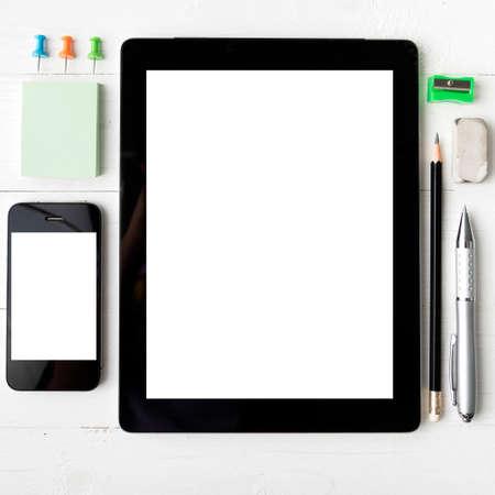 articulos de oficina: tableta y teléfono móvil con equipos de oficina sobre la mesa blanca Foto de archivo