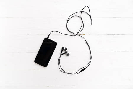 earphone: cellphone with earphone over white table Stock Photo