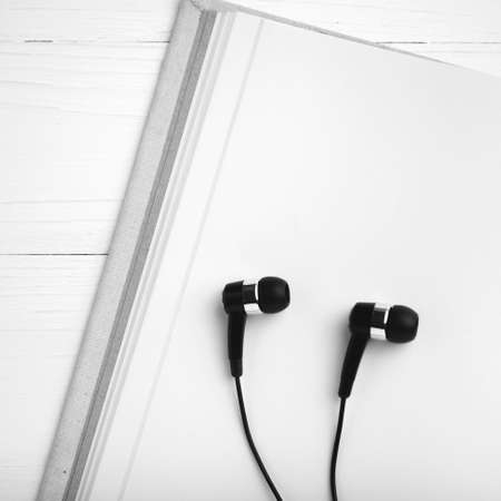 ear phone: notebook and ear phone over white table black and white color style Stock Photo