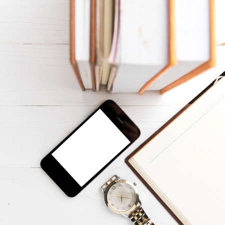 watch over: cellphone with stack of book and watch over white table
