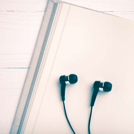 ear phone: notebook and ear phone over white table vintage style Stock Photo