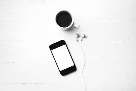 cellphone and coffee cup over white table black and white color style