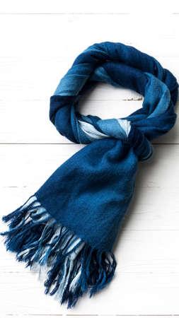 bufanda azul sobre la mesa de madera de fondo blanco Foto de archivo