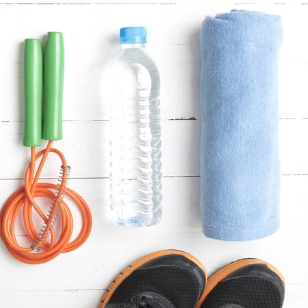 fitness equipment : running shoes,towel,jumping rope and drinking water on white wood table Reklamní fotografie