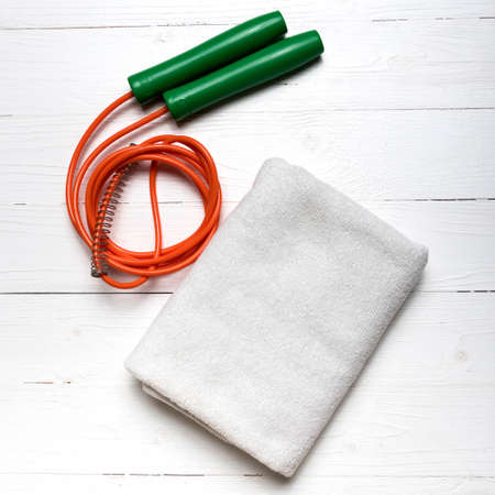 white towel: fitness equipment:white towel,jumping rope on white wood table