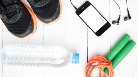 water bottles: fitness equipment : running shoes,jumping rope,phone and water bottle on white wood table Stock Photo