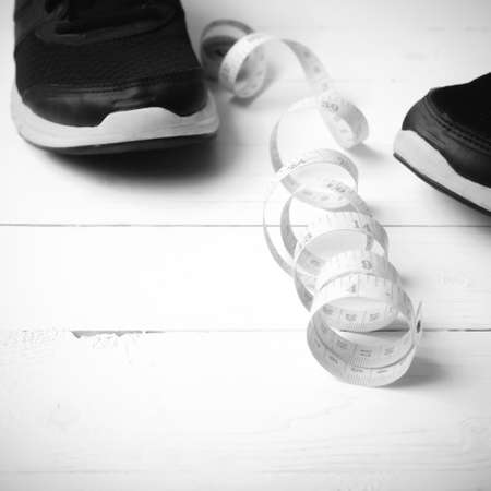 athletic wear: running shoes and measuring tape on white wood table black and white tone color style
