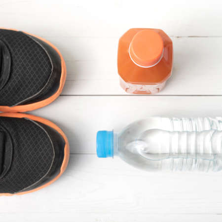 running shoes,drinking water and orange juice on white wood table Stock Photo