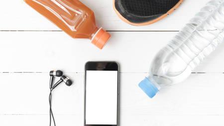 manzana agua: zapatos para correr, zumo de naranja, agua potable y tel�fono en el fondo de madera blanca