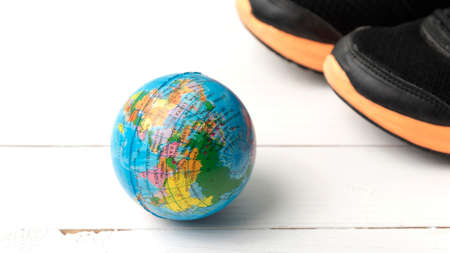 running shoes and earth ball on white wood table concept world healthy