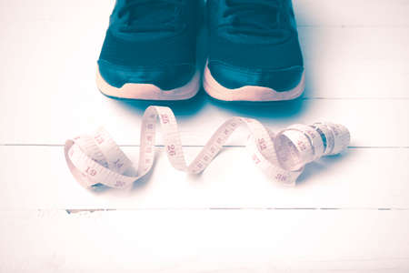 athletic wear: running shoes and measuring tape on white wood table vintage style