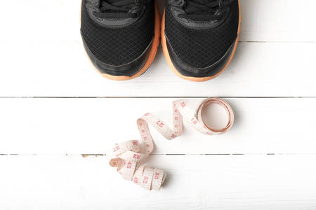 athletic wear: running shoes and measuring tape on white wood table