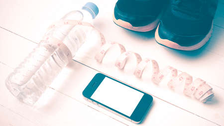 fitness equipment : running shoes,drinking water,measuring tape and phone on white wood table vintage style Stock Photo