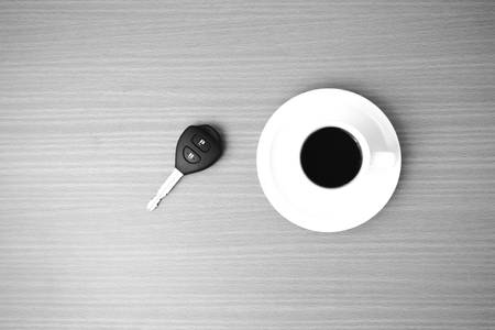 color key: coffee cup and car key on wood background  black and white color