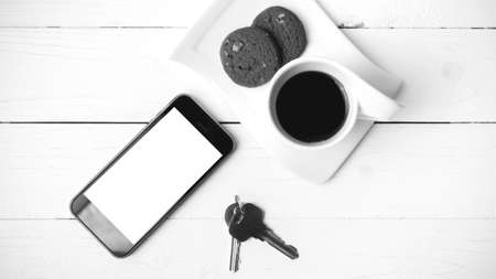 travel mug: coffee cup with cookie,phone and key on white wood table black and white color