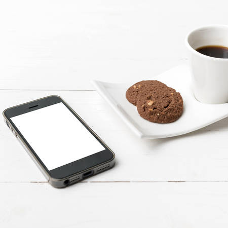 breakfast coffee: coffee cup with cookie and phone on white wood background