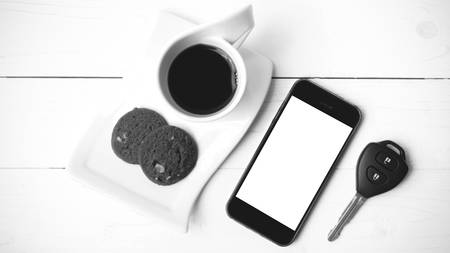 travel mug: coffee cup with cookie,phone and car key on white wood table black and white color Stock Photo