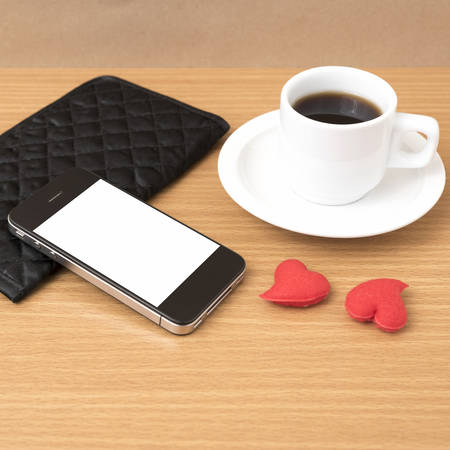 beverage display: coffee,phone,wallet and heart on wood table background