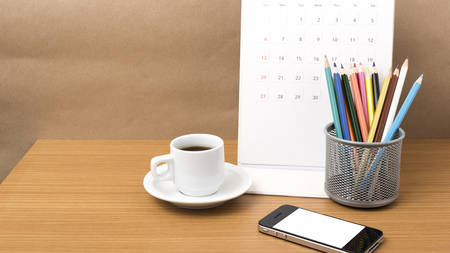 coffee,phone,calendar and color pencil on wood table background Imagens