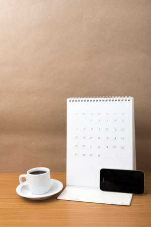 coffee cup and phone and calendar on wood background Imagens
