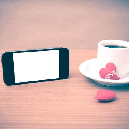 love letter: taza de café y el teléfono y el corazón en la madera estilo fondo de la vendimia