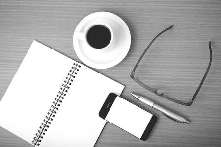 millennial: coffee,phone,notepad and eyeglasses on wood table background black and white color