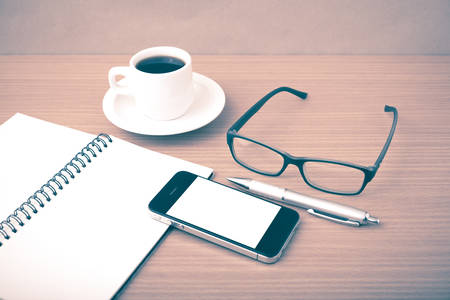 millennial: coffee,phone,notepad and eyeglasses on wood table background vintage style Stock Photo