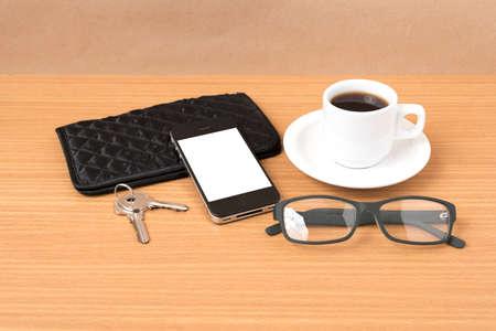 eyeglasses: coffee,phone,key,eyeglasses and wallet on wood table background