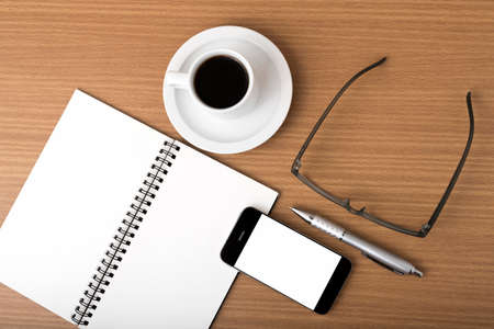 millennial: coffee,phone,notepad and eyeglasses on wood table background Stock Photo