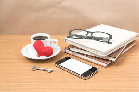 mug of coffee: office desk : coffee and phone with key,eyeglasses,stack of book,heart on wood background