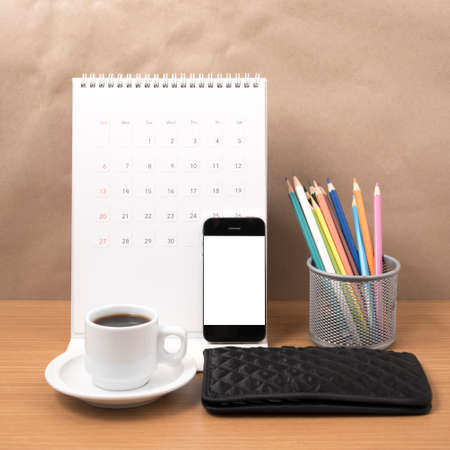 office desk : coffee with phone, calendar, wallet, color pencil on wood background