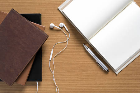 audio book: top view of stack of notebook with earphone on wood background concept audio book Stock Photo