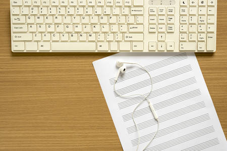 music staff: top view of music staff paper note computer keyboard and earphone on wood background concept computer music Stock Photo