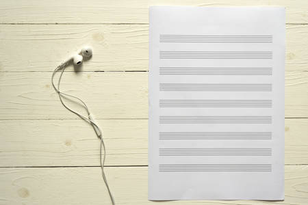 music staff: top view of music staff paper and earphone on wood backgroud