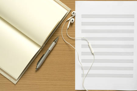 music staff: top view of music staff notebook and earphone on wood background