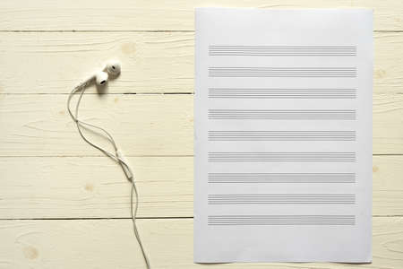 music staff: music staff paper with earphone on white wood background