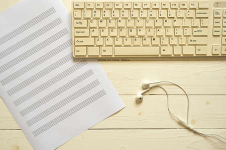 music staff: top view of computer keyboard earphone and music staff paper on white wood background Stock Photo