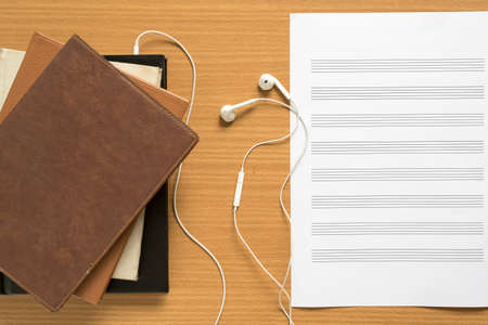 music staff: top view of stack of notebook with earphone and music staff paper on wood background