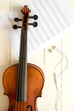music staff: top view of violin and music staff with earphone on white wood background